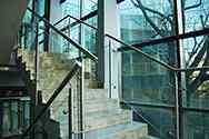 Stainless steel glass balustrade with satin finish, tubular handrail and posts, toughened glass filling