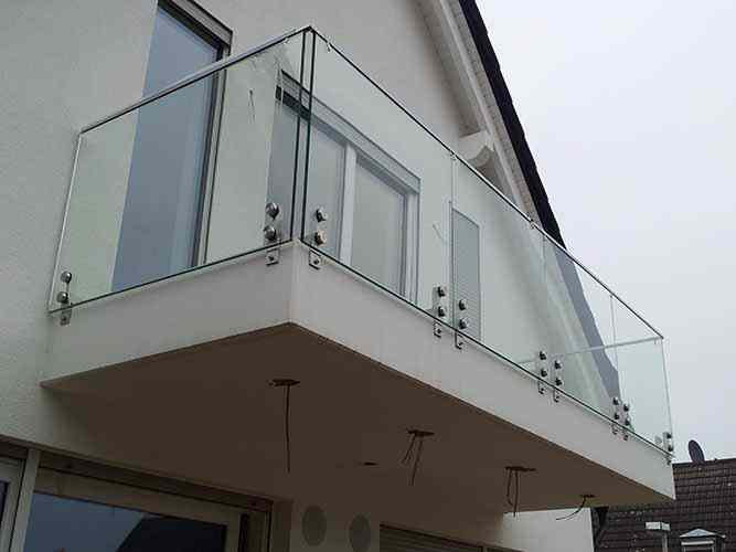 Frameless glass balustrade with stainless steel top rail on balcony.