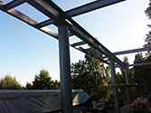 The upper frame of the supporting structure with a balcony frame mounted to it and resting on a row of steel poles