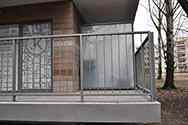 Balcony balustrade from galvanized, powder painted steel with bar infill. Stainless steel flashings around the balcony plate.